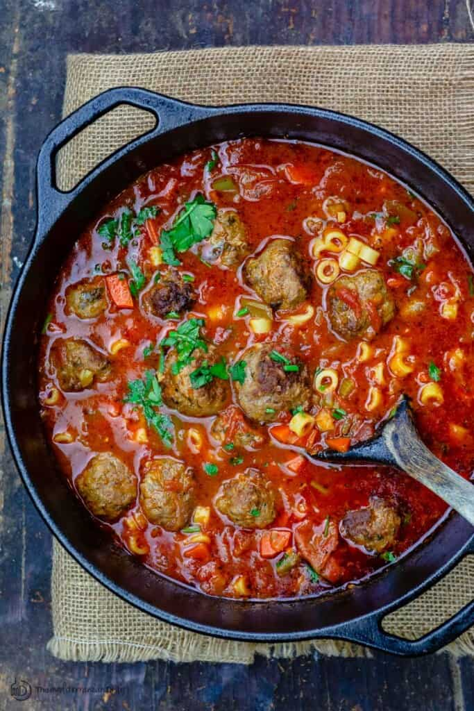 Italian meatball soup in large pot with ladel