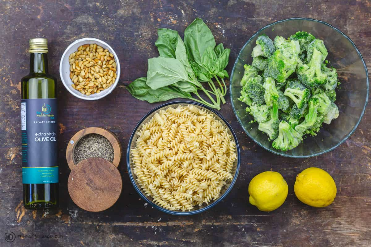 ingredients for pesto pasta: pasta, broccoli, lemon, basil leaves, pine nuts, pepper, parmesan cheese, olive oil