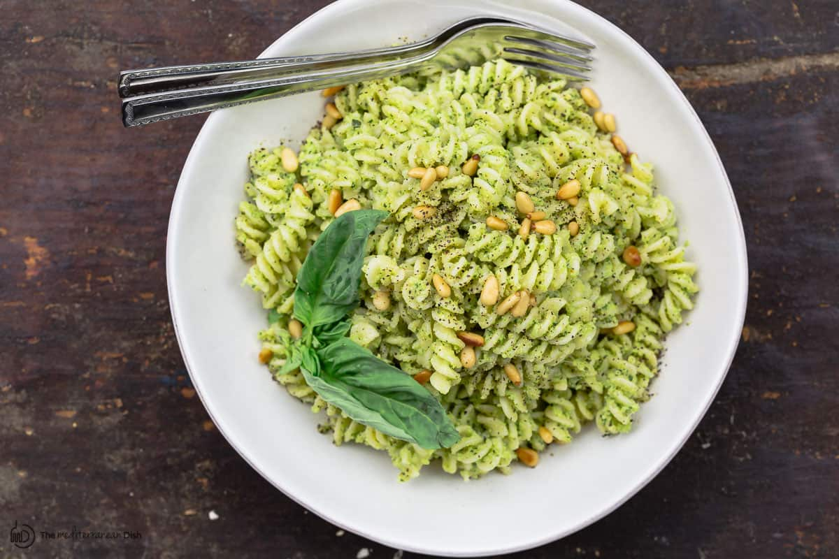Pesto pasta served in a bowl with forks and fresh basil for garnish