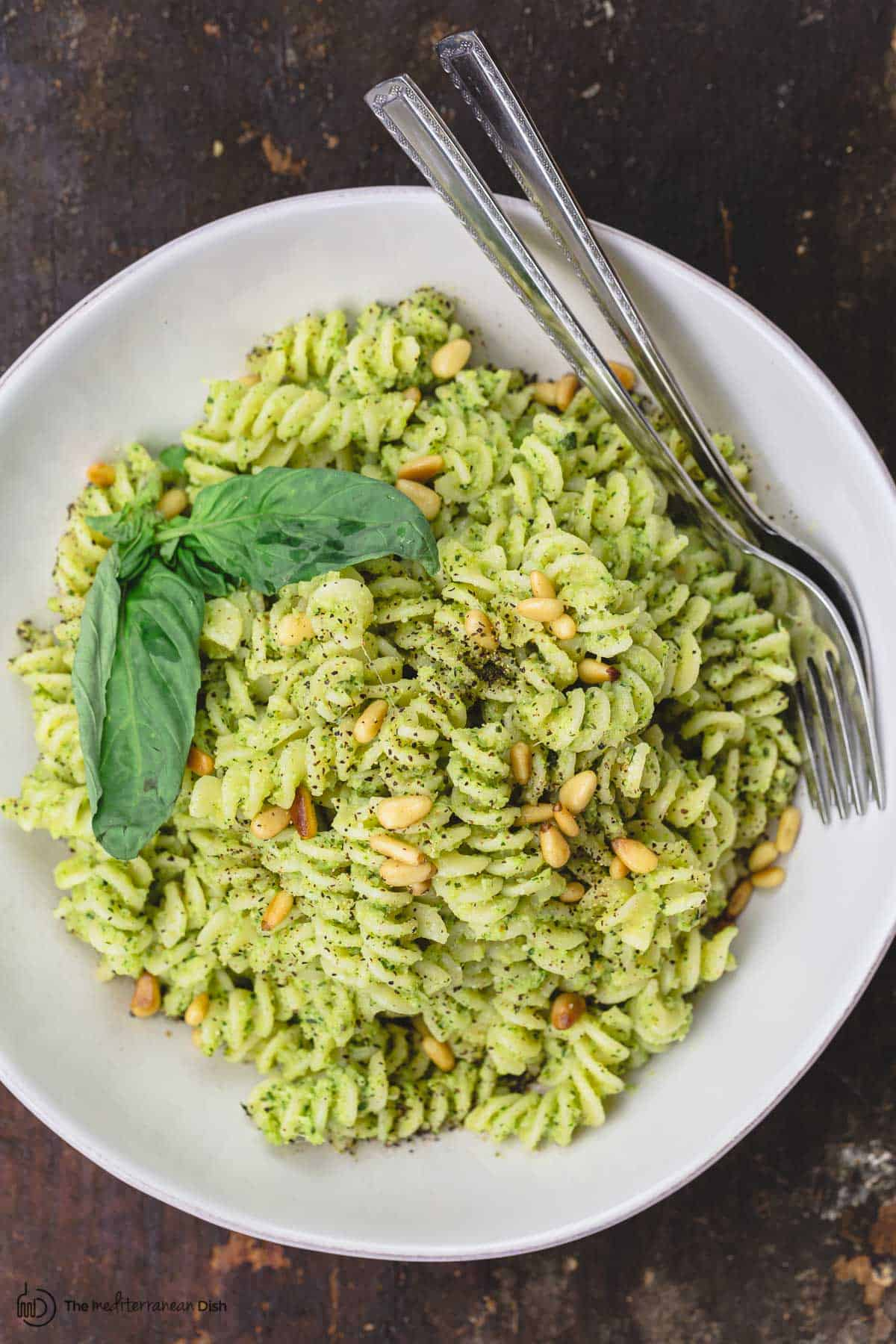 A bowl of broccoli pesto pasta with pine nuts and basil