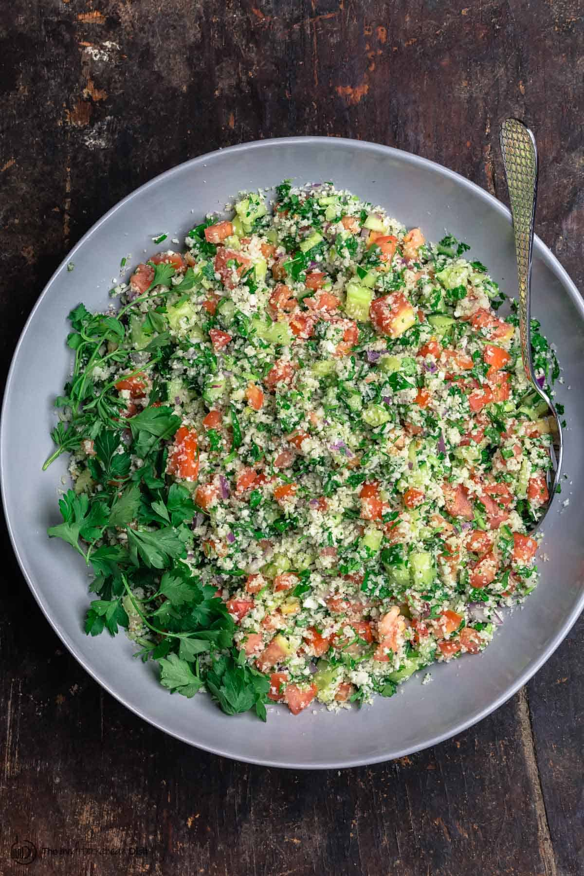Mediterranean cauliflower salad with tomatoes, cucumbers, parsley and red onions, served in a large bowl