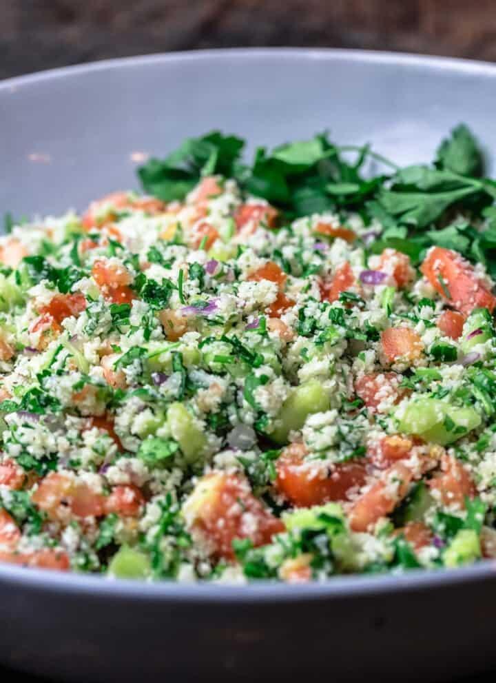 cauliflower salad in a large bowl with fresh parsley for garnish