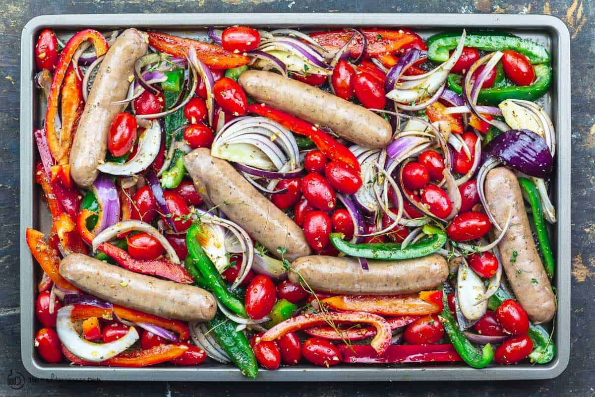 veggies and sausage spread on one sheet pan before baking
