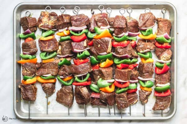 uncooked beef kabobs on a tray ready for grilling