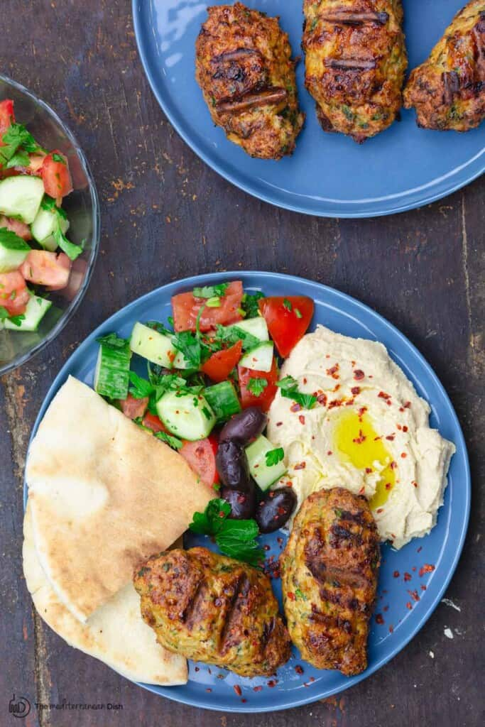 Two plates of chicken kofta patties with a side salad and hummus