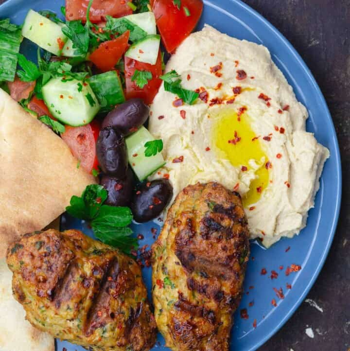 two chicken kofta with hummus, salad and pita on blue plate for serving