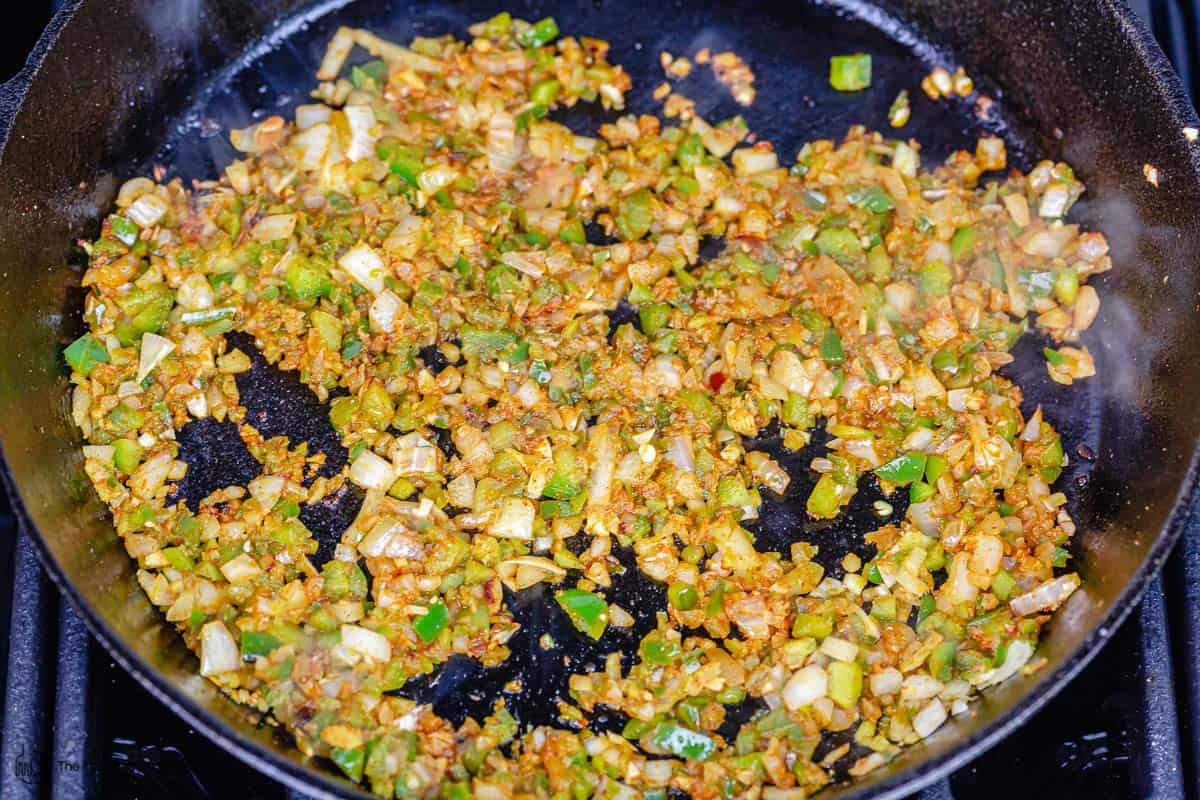 bell peppers, onions, garlic and spices cooking in skillet
