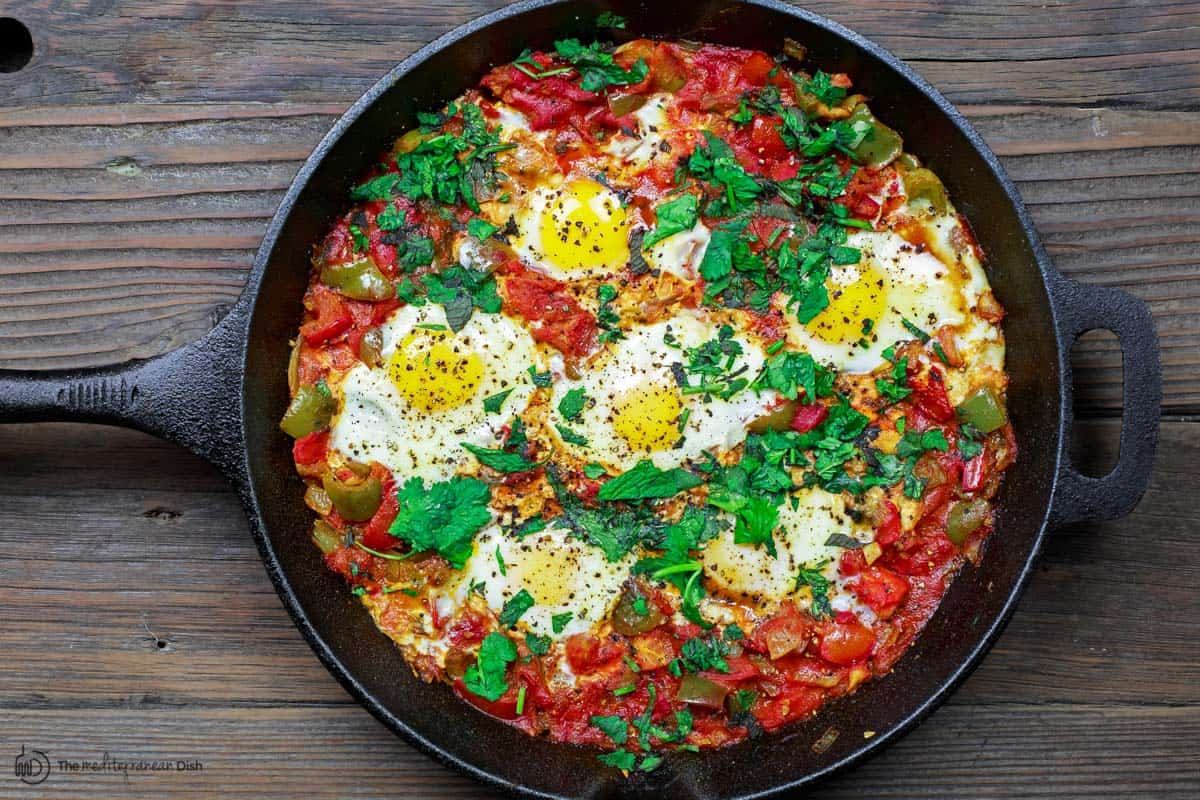cooked shakshuka recipe with garnish of parsley and mint