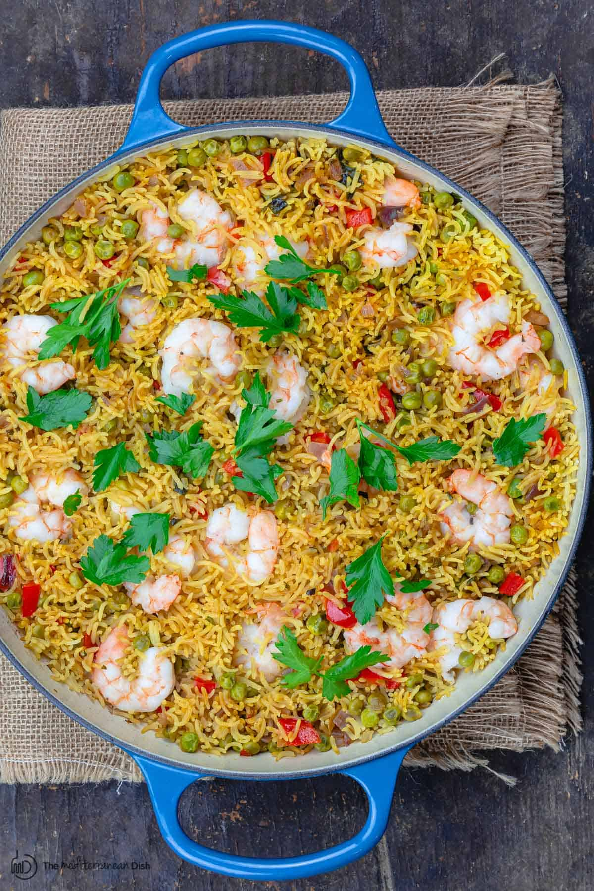 shrimp and rice in a blue pan. Garnished with parsley