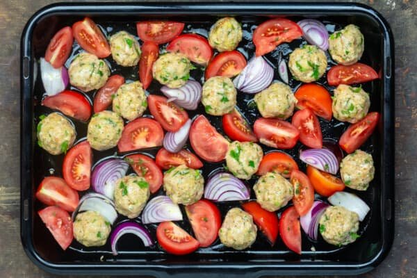 chicken meatballs arranged with tomatoes and onions on sheet pan before baking