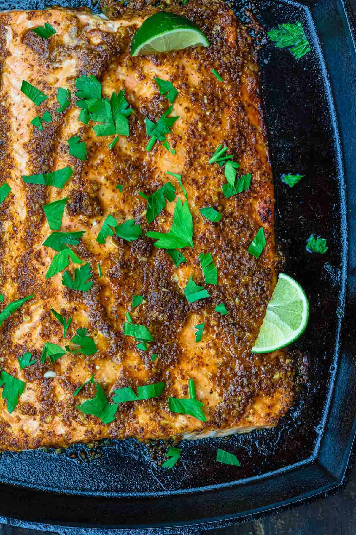 honey mustard salmon garnished with parsley and sliced lime
