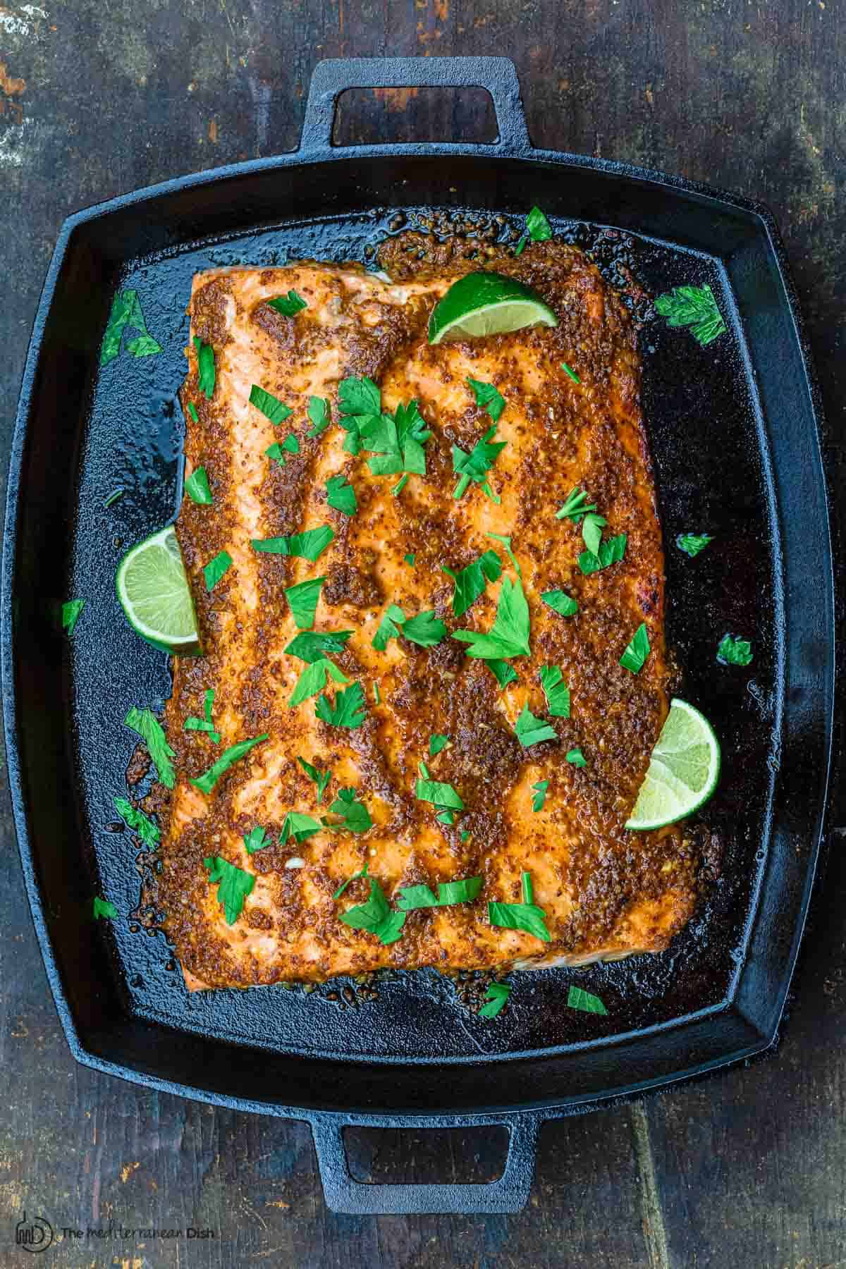 honey mustard salmon recipe in pan with lime wedges