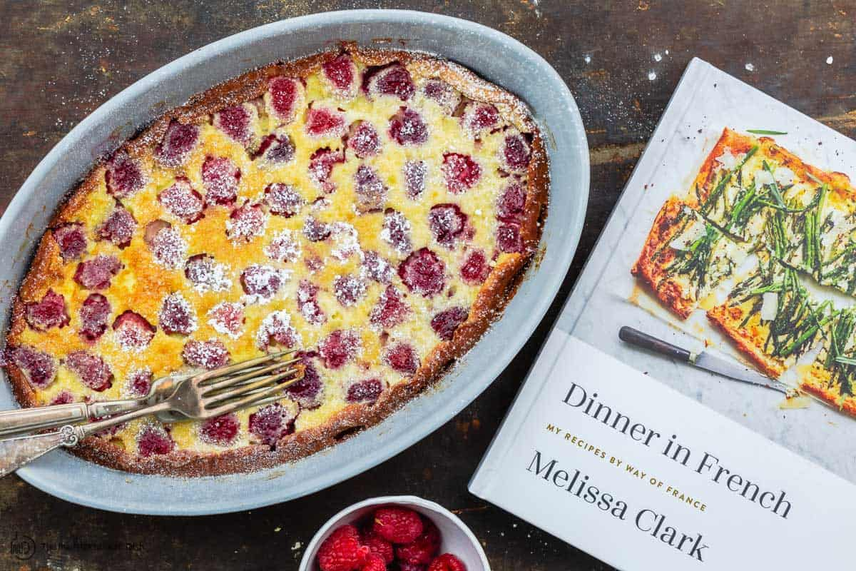 clafoutis next to a copy of Melissa Clark's book Dinner in French