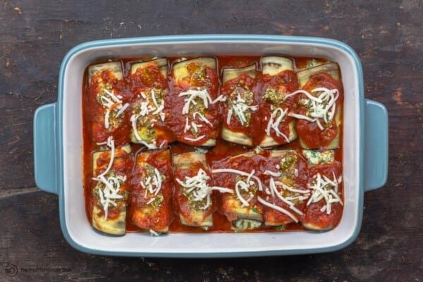 eggplant roll ups topped with sauce and mozzarella cheese