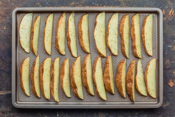 raw potato wedges arranged on sheet pan