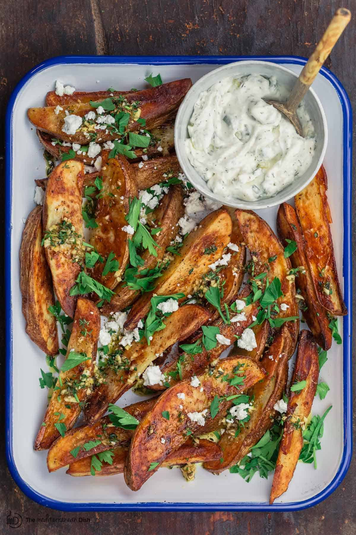 Oven fries with feta cheese and a side of tzatziki sauce