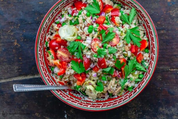 Rice salad served in a large red bowl