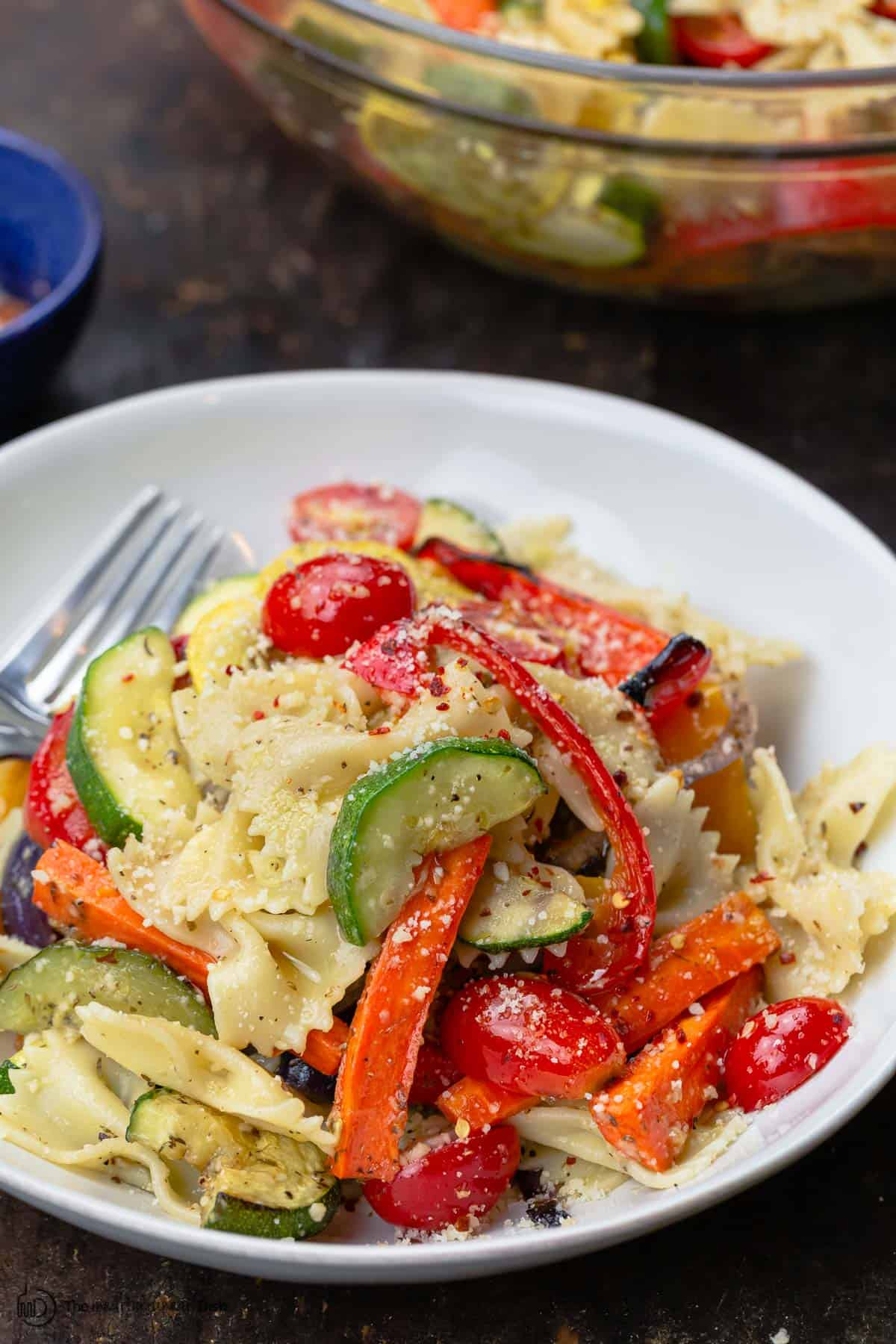 Pasta primavera with roasted veggies in a bowl. A large serving bowl to the side
