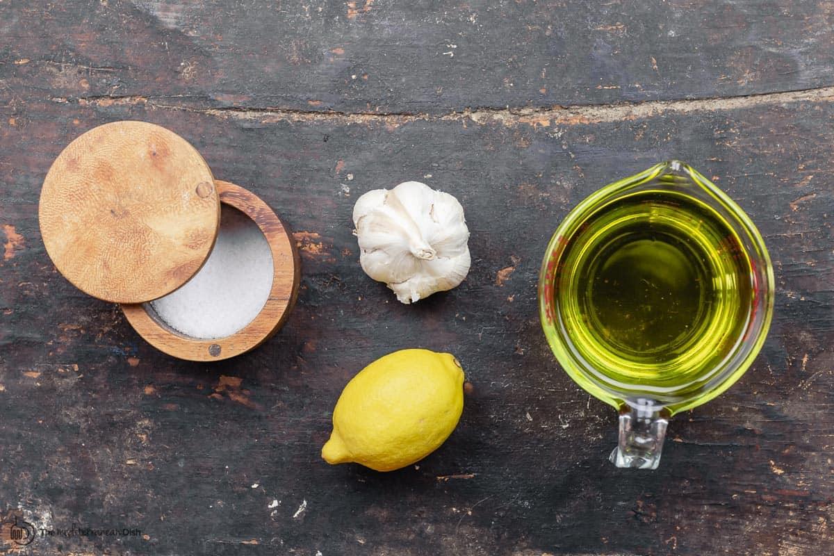 ingredients for toum recipe: garlic, lemon, oil, and salt