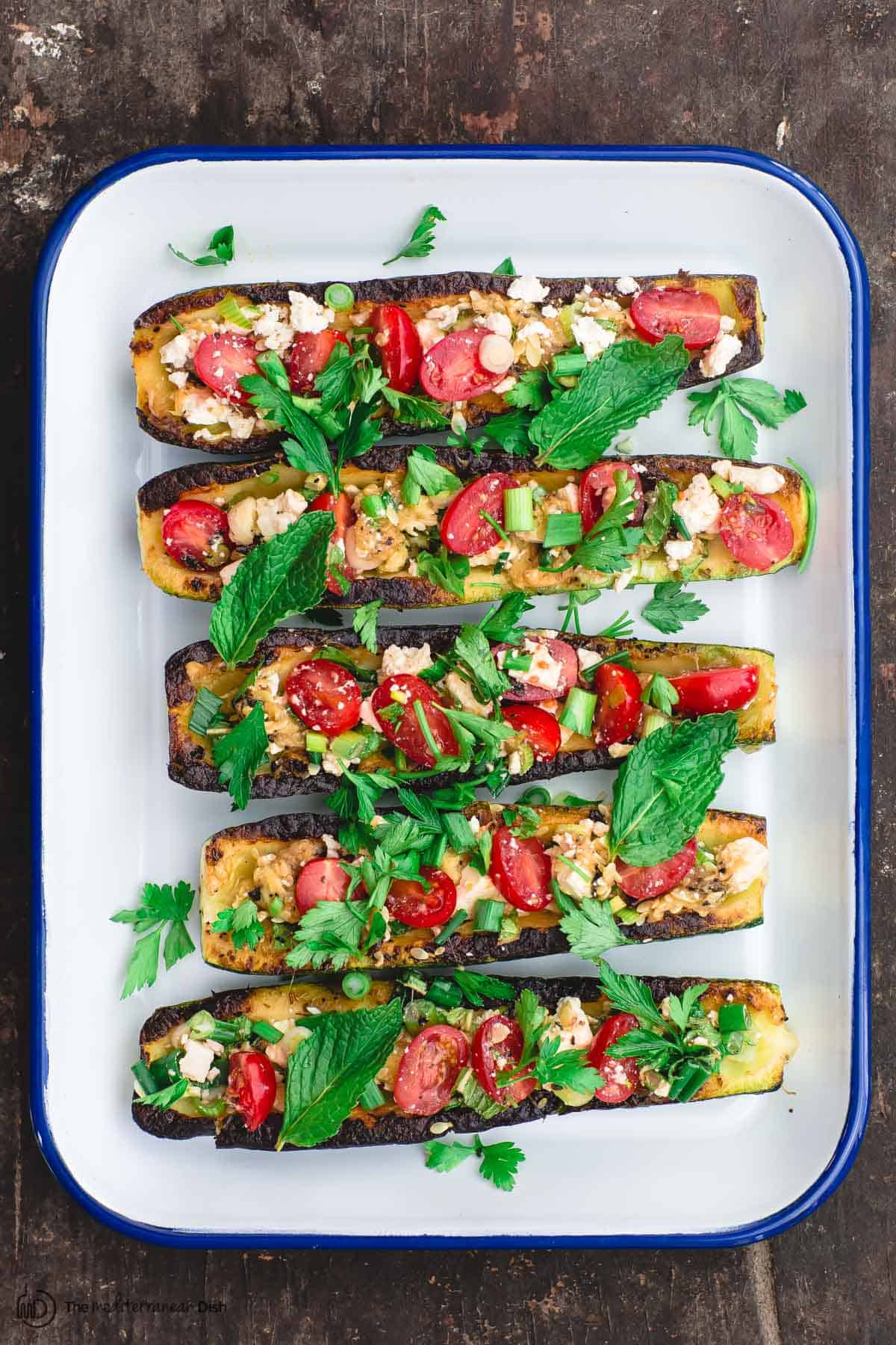 zucchini boats topped with tomatoes and feta