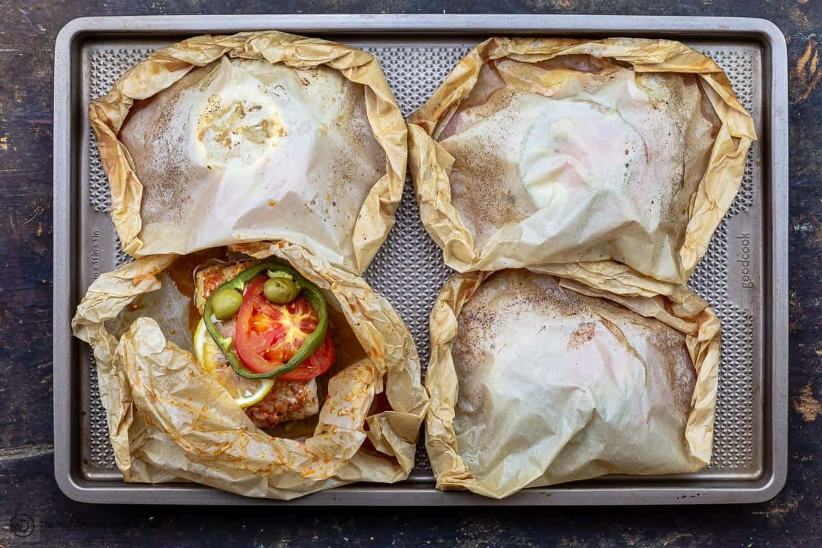 cooked fish en papillote on a baking sheet
