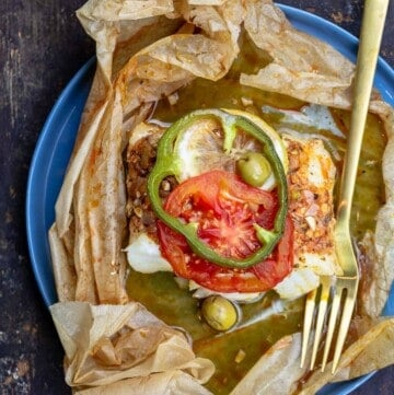 fish en papillote topped with green peppers and tomatoes