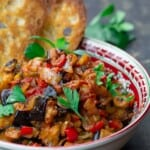 eggplant caponata served in a bowl with toasted ciabatta bread