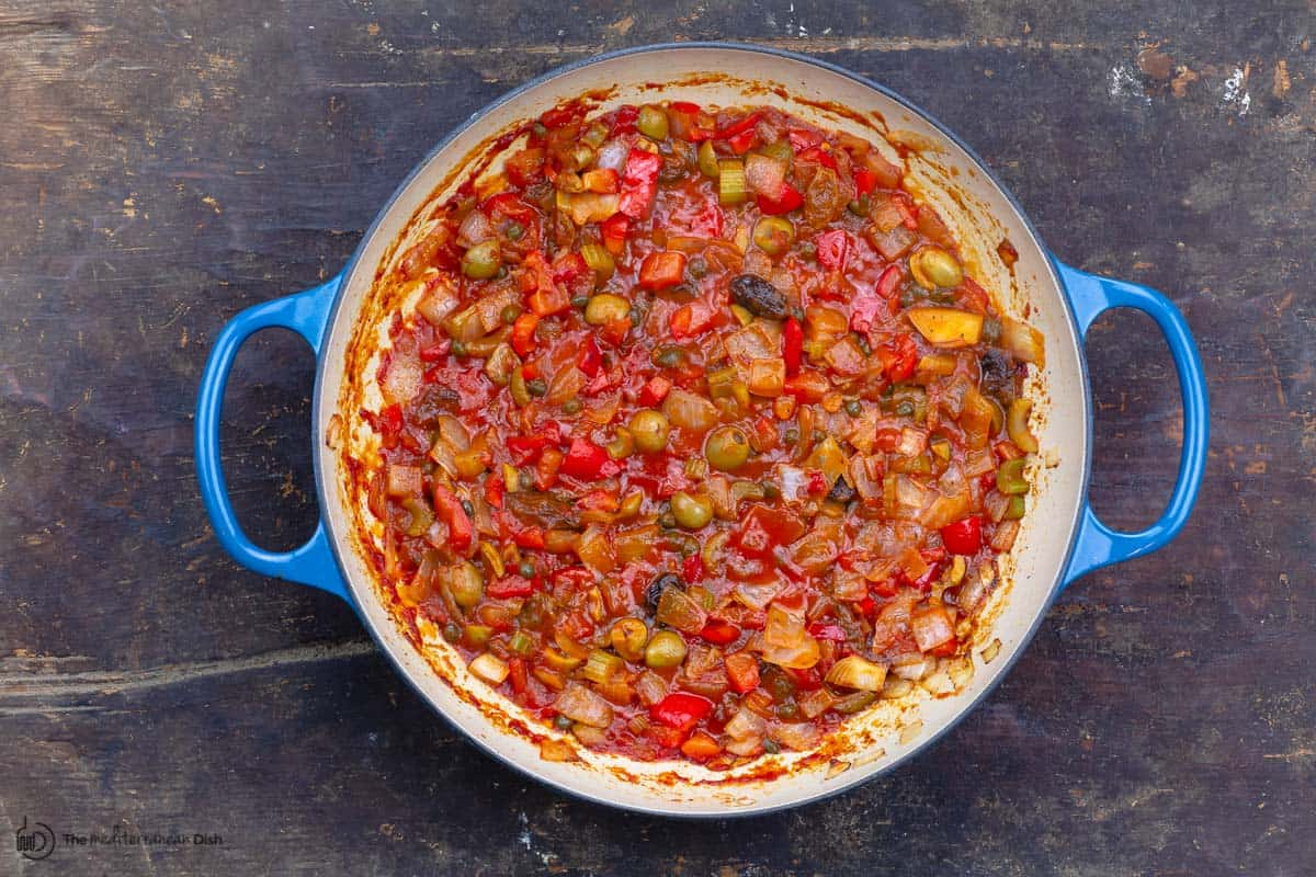 tomato sauce, olives and the remaining ingredients are added to the pan