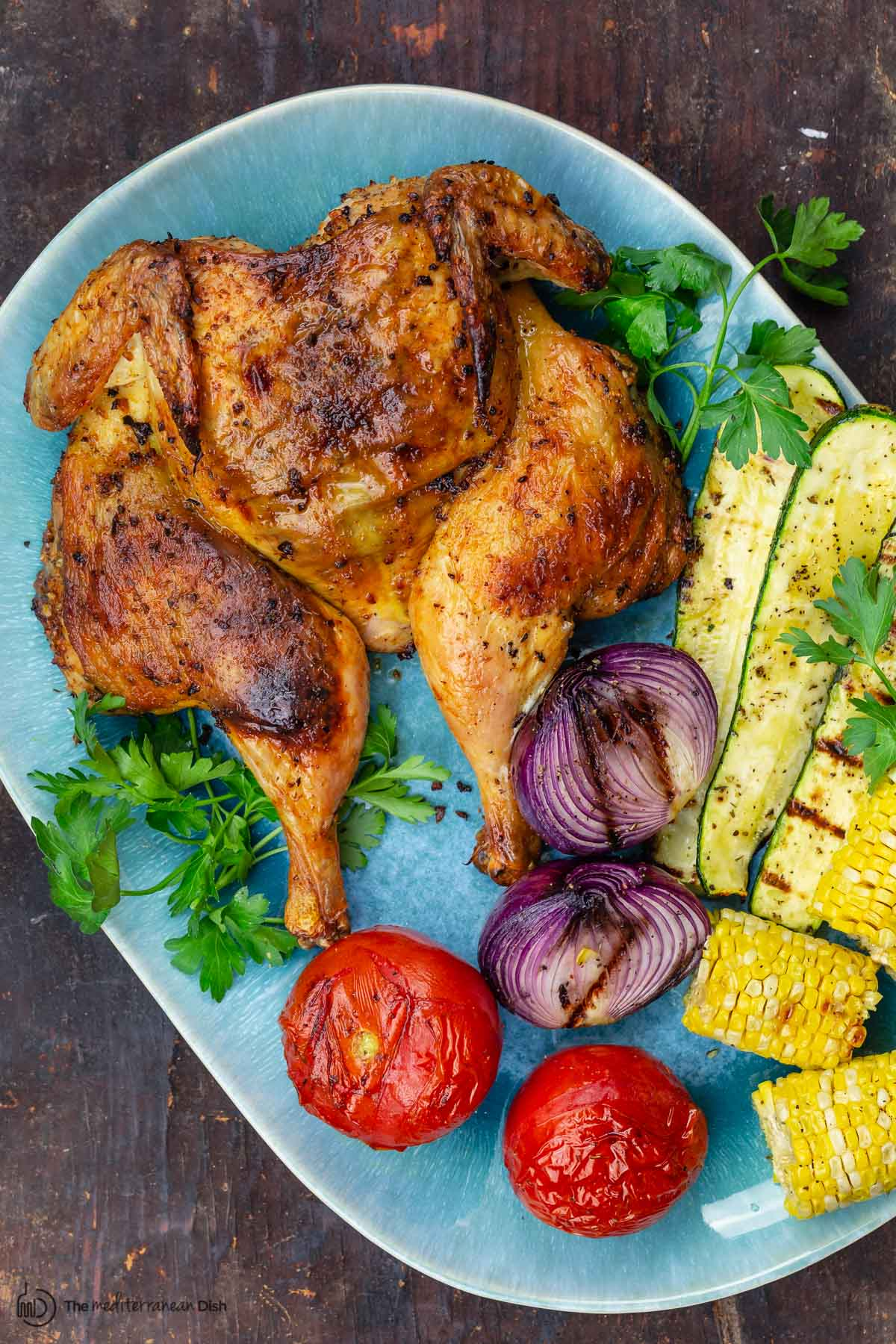 grilled whole chicken with grilled vegetables on a serving platter