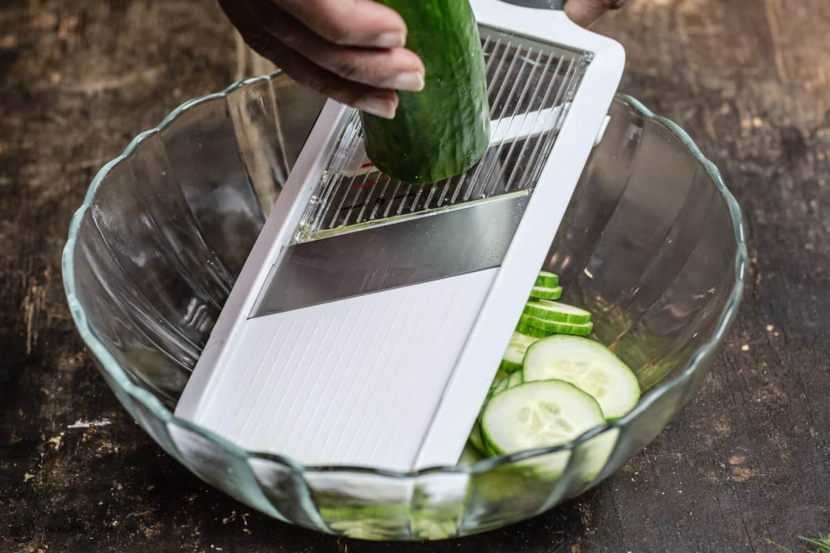 cucumbers being sliced using a mandoline