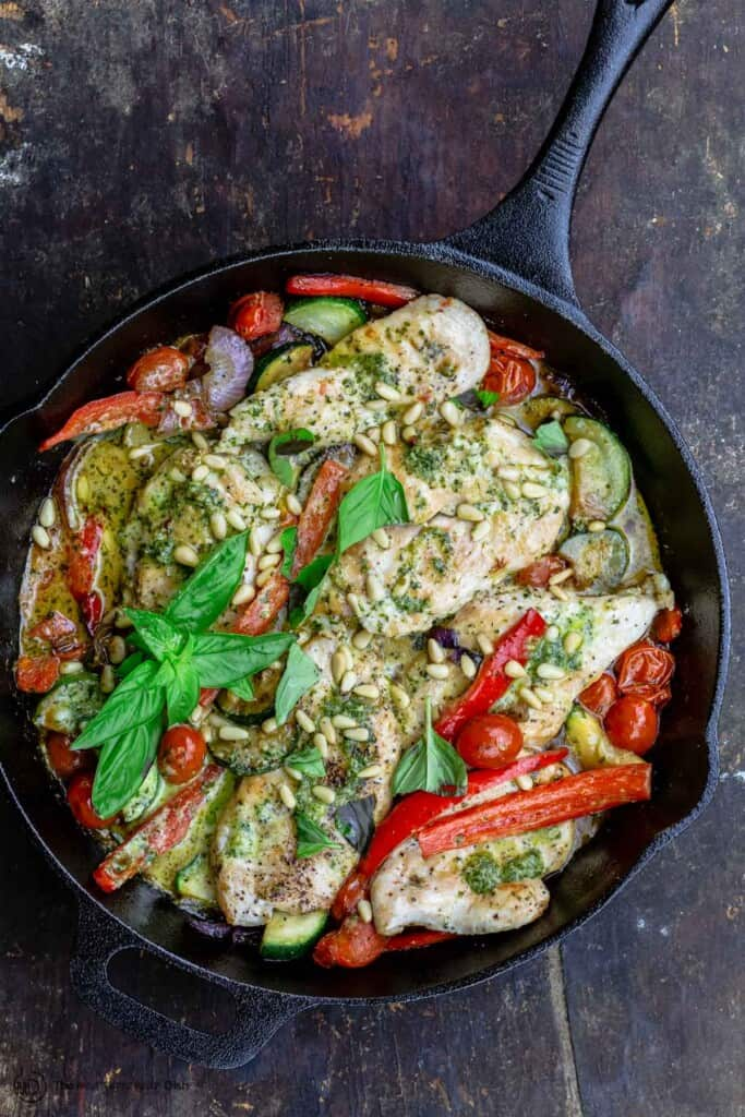 pesto chicken and vegetables in a pan