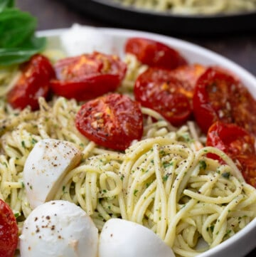 Pasta in a large bowl, tossed with pesto, tomatoes and mozzarella. A small plate to the side