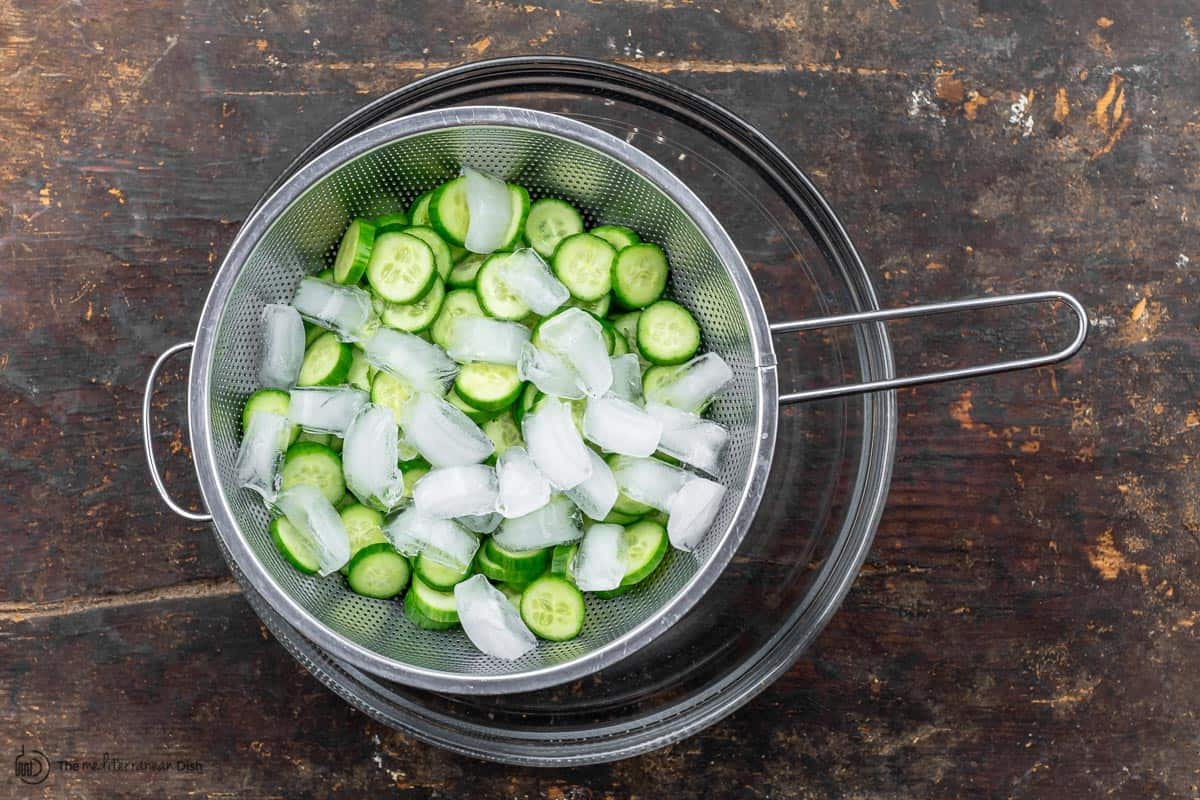 cucumber slices and ice in colander