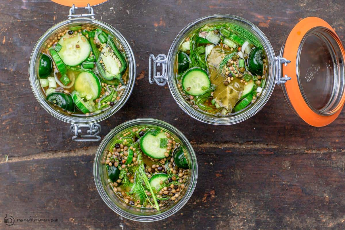 three open jars of pickled cucumbers