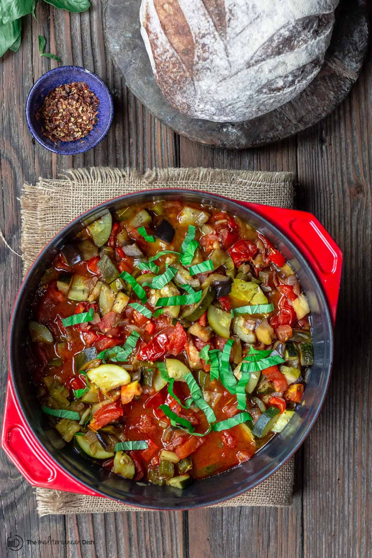 Rataouille served in a large red pot on a table with a loaf of bread