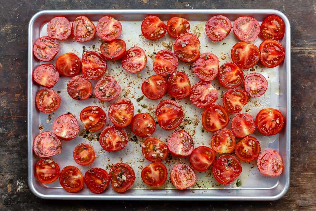 raw tomato halves spread on a sheet pan. Tomato flesh facing up