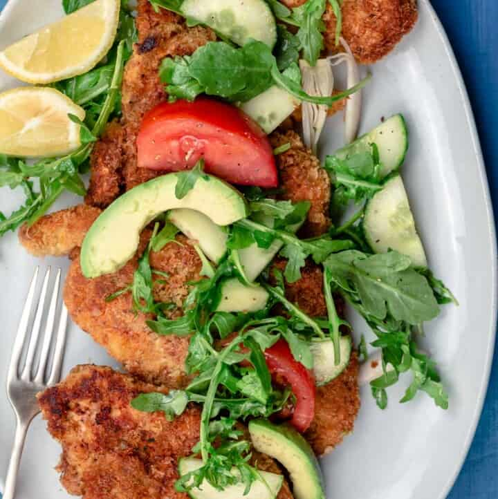 Chicken schnitzel served with arugula salad and lemon juice