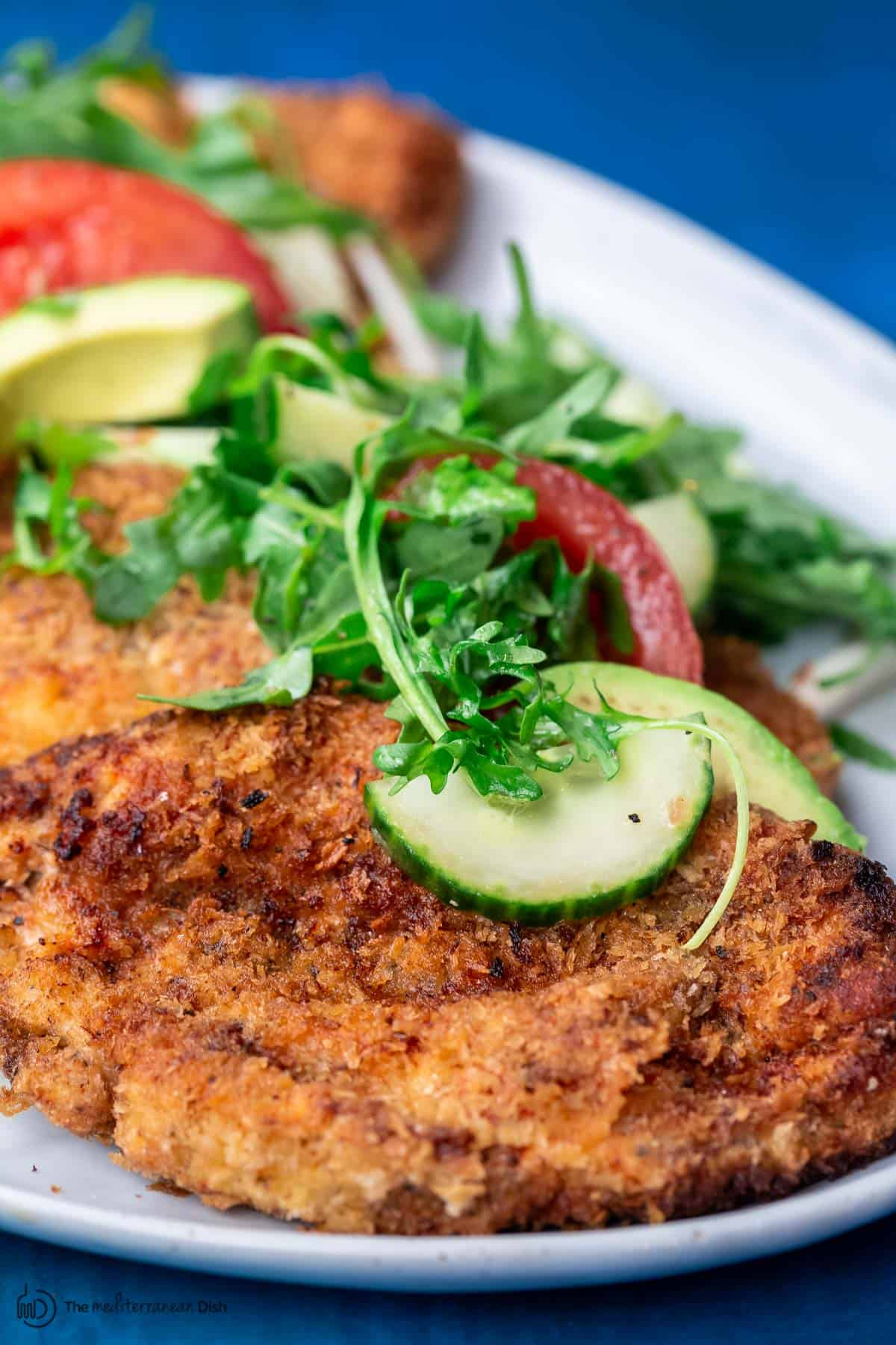 chicken schnitzel on a platter with arugula salad