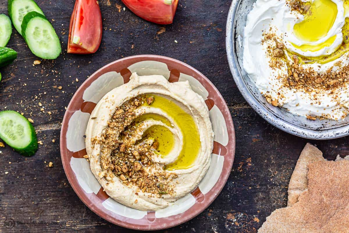 dukkah sprinkled over hummus and labneh with a side of veggies and bread
