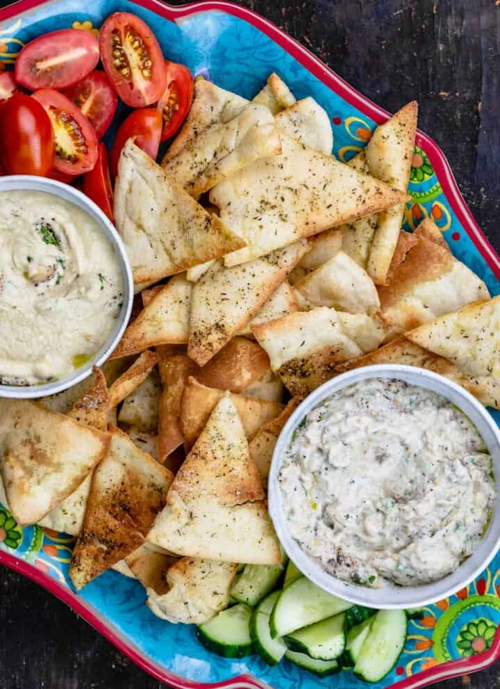 Homemade pita chips as part of mezze platter with two dips and veggies
