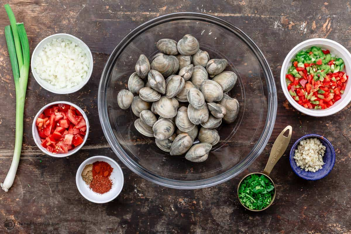 Ingredients for steamed clams recipe. clams, onions, garlic, spices, fresh herbs