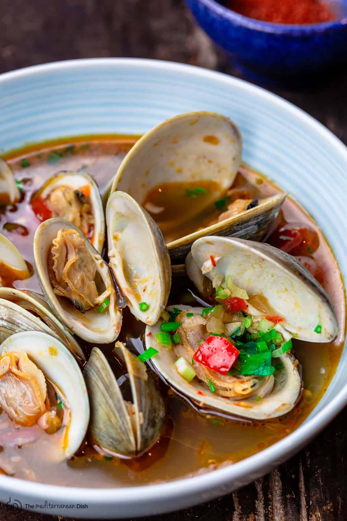 Steamed clams with broth in a serving bowl