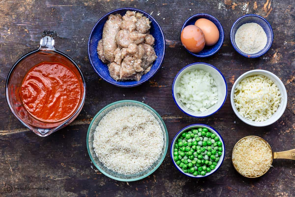 casserole ingredients including rice, sausage, peas, cheese, eggs, marinara sauce