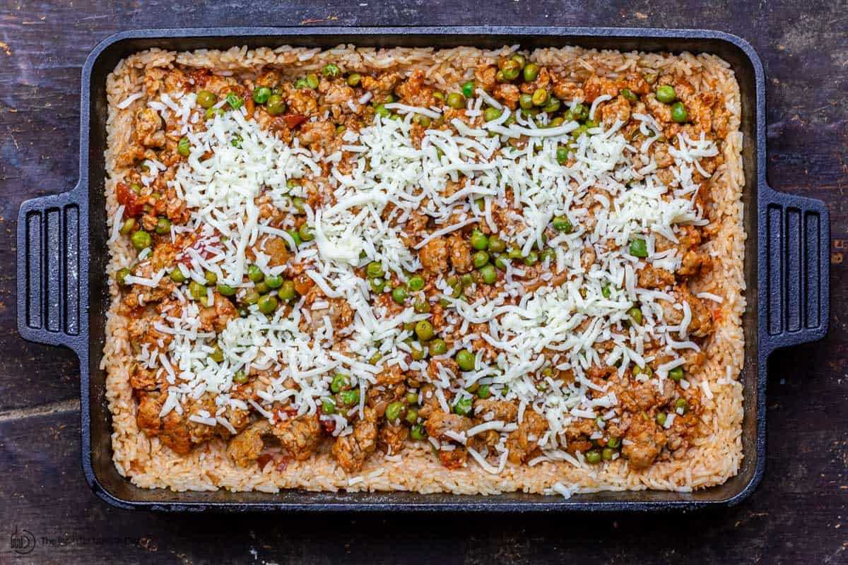Layers of rice, sausage and peas in a baking dish