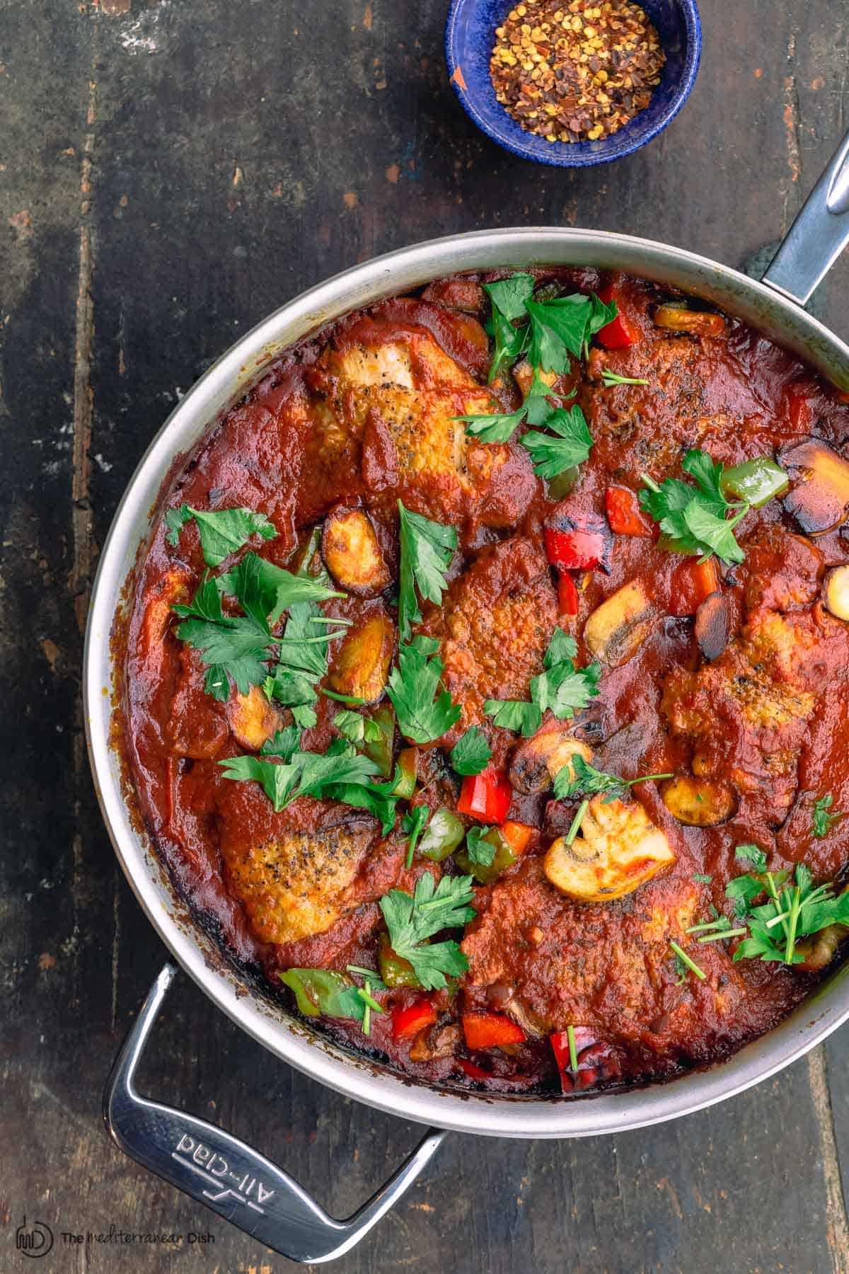 cacciatore with a side of red pepper flakes in a bowl
