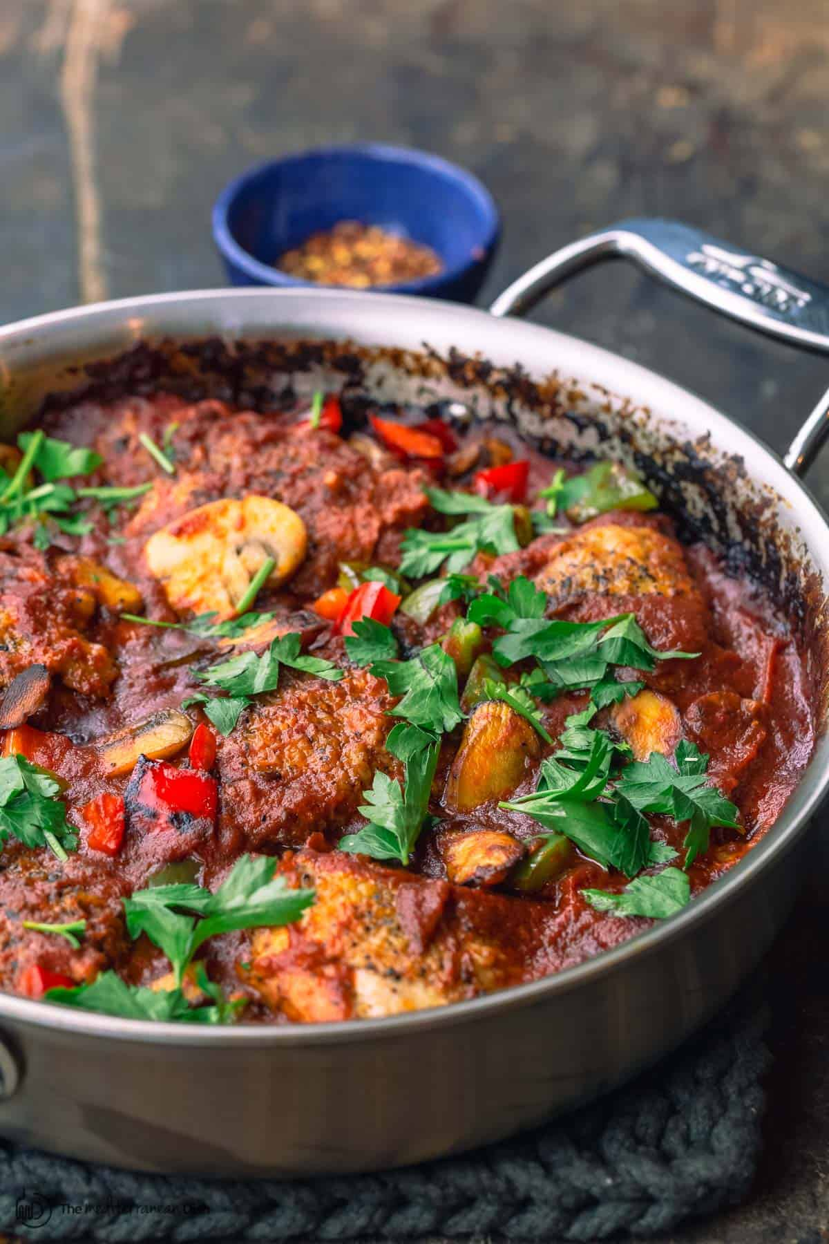 one pan chicken cacciatore with a small bowl of red peppers