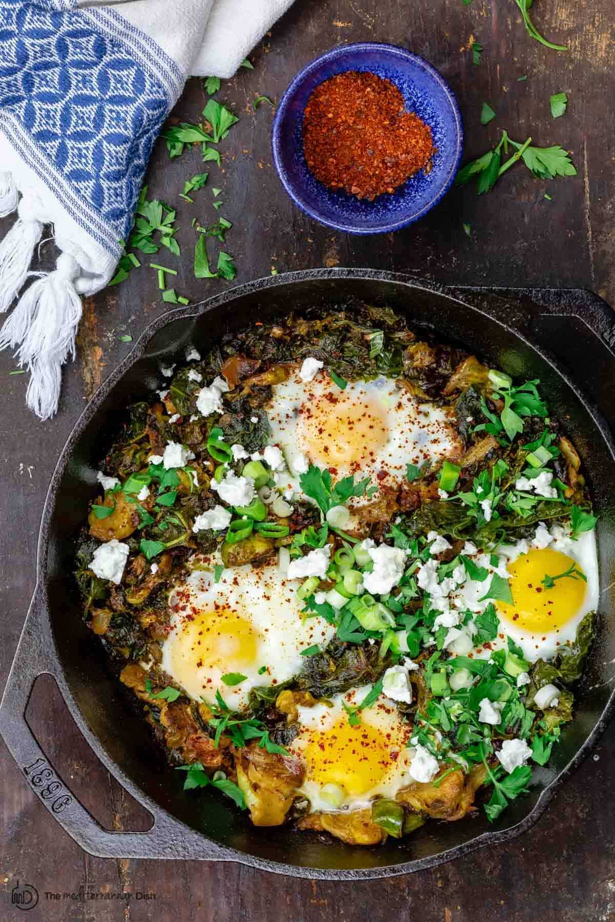 Green shakshuka served with parsley and feta cheese with a side of Aleppo chile pepper flakes