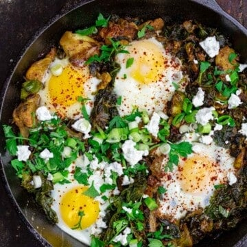 Green shakshuka in skillet with spinach and kale. Topped with feta