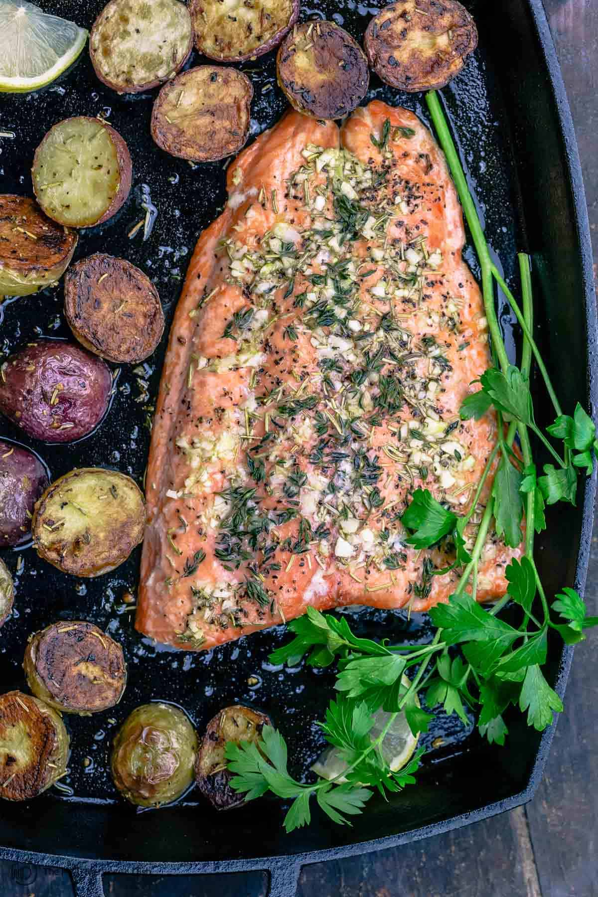 Slow roasted salmon in pan with potatoes and parsley