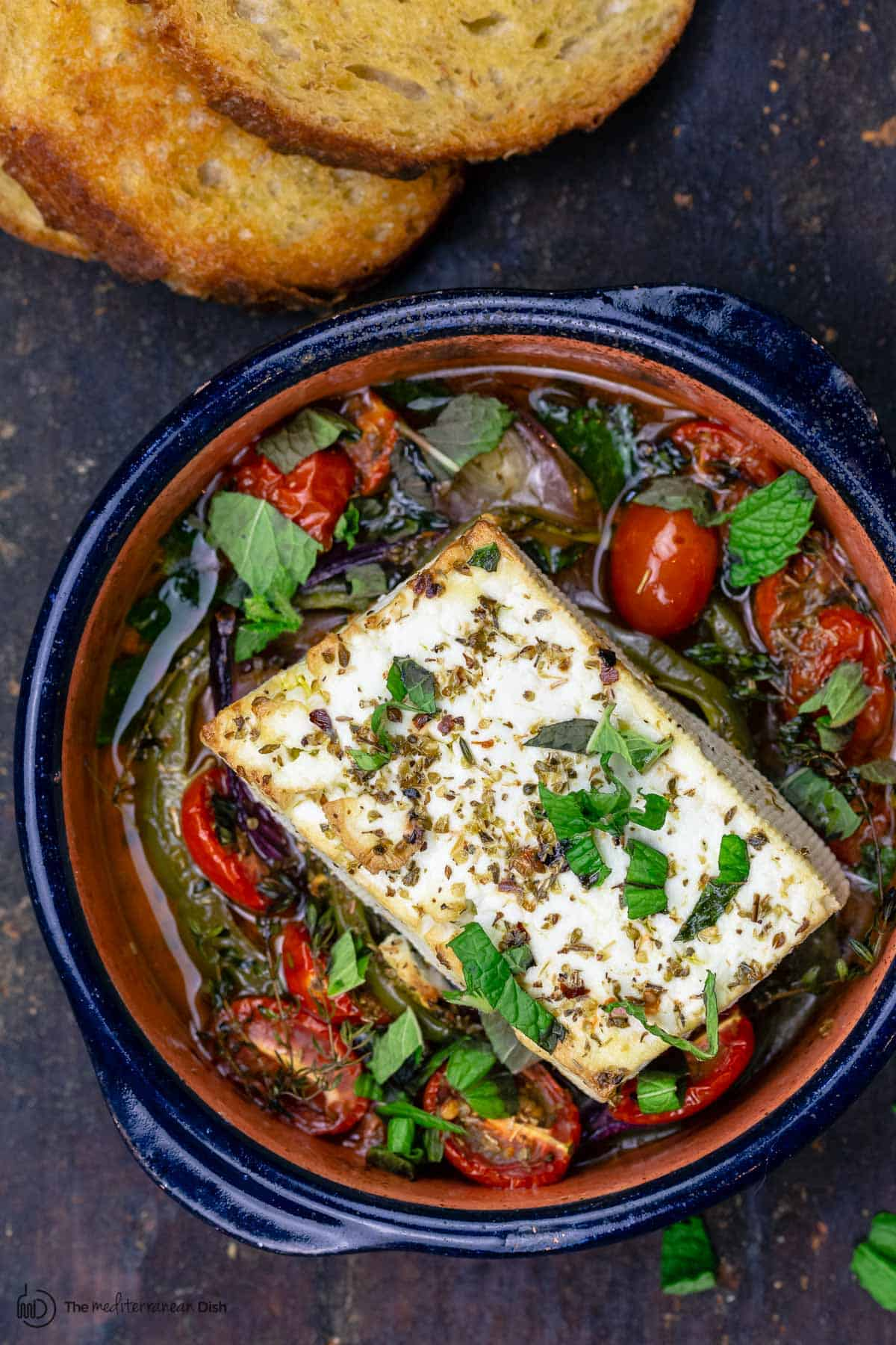 Baked feta served with a side of toasted bread
